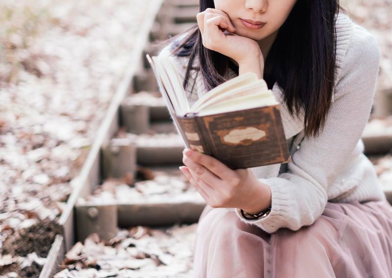 日記帳を見て先月の行動を振り返る女性